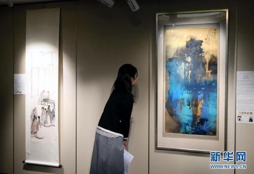3月14日,一位记者在香港苏富比春拍记者会上观看张大千的泼墨泼彩山水画作《?霍瑞霭》。香港苏富比将于4月4日举行中国书画专场拍卖会,呈献逾300幅中国近现代书画佳作,总估值约1.6亿港币。 新华社记者 李鹏 摄