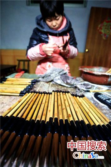 河南省项城市孙店镇汝阳刘村制笔艺人刘付林的爱人在给毛笔上浆。(中国搜索 杨正华 摄)