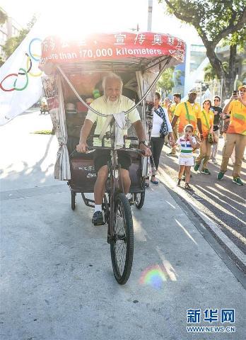 """7月31日,陈冠明在马拉卡纳体育场外骑行。 当日,在里约奥运会开幕式举办地马拉卡纳体育场,一名特殊的中国游客神奇亮相,他就是被称为""""奥运狂人""""的60岁江苏籍农民陈冠明。陈冠明自2001年北京申奥成功后便开始骑行世界,""""奥运到哪里,我就到哪里。"""" """"这是我的交通工具,也是我睡觉的帐篷。""""他指着喷印着满满新闻报道的三轮车说。15年骑行追逐奥运,他从早期的为北京奥运会造势转变到如今的行走全球体验奥运文化。陈冠明说,他于30日来到里约,计划在这座城市逗留20余天,奥运会闭幕后,他将骑往大洋洲。"""