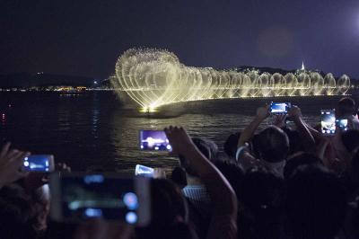 8月24日,游客在西湖边欣赏西湖音乐喷泉。