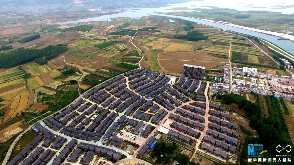 """陶岔村是河南省南阳市淅川县九重镇下辖的一个行政村,世界上最大的自流引水工程南水北调中线工程的组成部分陶岔渠首枢纽工程就位于该村。近年来,为改善陶岔村群众的生活质量,淅川县大力打造""""渠首第一村""""这一旅游金字招牌。2013年5月18日,陶岔村启动了""""安居乐业新民居改造项目"""",打造宜居宜业宜旅的绿色文明""""风情小镇""""。目前,一个集旅游、商贸、餐饮、住宿于一体的""""风情小镇""""已成为渠首一道亮丽的风景。(牛书培 摄)"""
