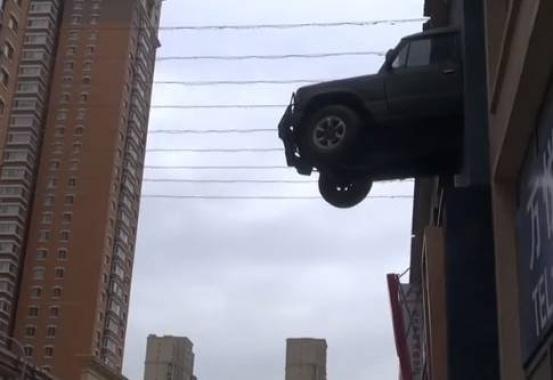 沈阳浑南某小区外越野车穿墙悬空 究竟咋回事?