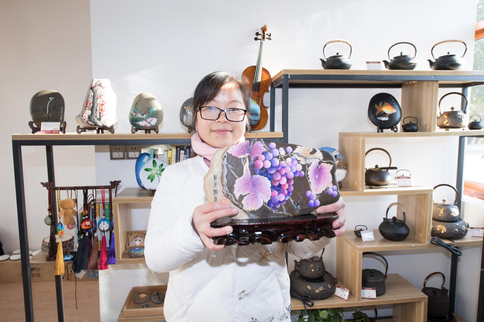 """""""农民画家""""陈苏兰在开设的工作室内展示创作的石头画《下姜葡萄》(1月10日摄)。新华社记者 翁忻旸 摄"""